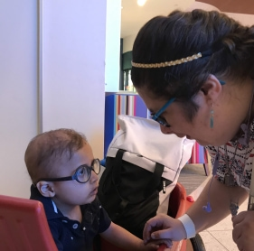 Image of young adult talking to young child with WAGR syndrome