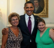 Amy and Shari standing with President Obama (his arms are around them both)