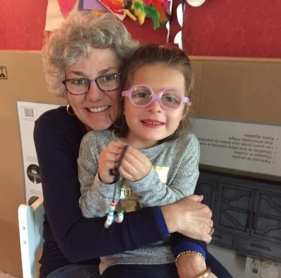 Image of woman embracing child with glasses