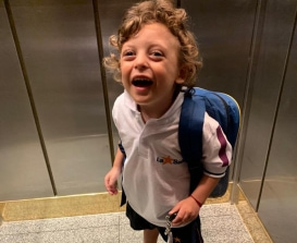 Image of child smiling with a backpack