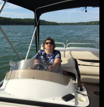 Girl with WAGR syndrome sitting in driver's seat of a boat