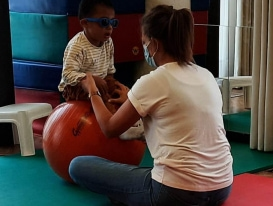 Image of child sitting on ball with teacher