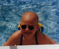 Amy in pool, with a big beautiful smile and a completely bald head